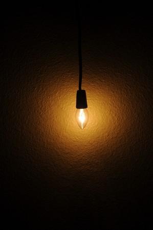 Una bombilla pequeña clara colgando junto a una pared