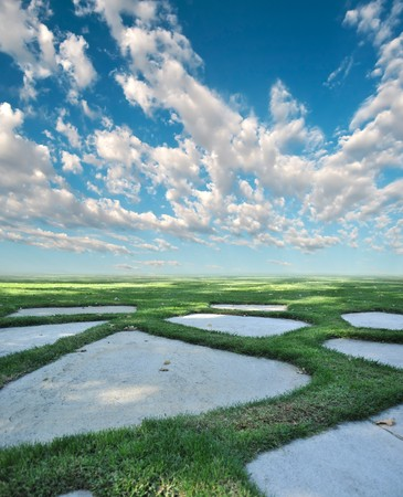 tile flooring: Garden stone path with grass growing between the flat masonry rocks with blue sky and clouds above the horizon with copyspace.