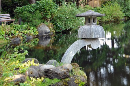 A zen cement lantern decoration above a garden pond.