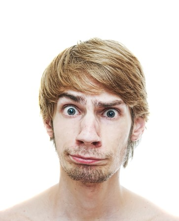 A young man caught in a dilemma looking into the camera with a confused look on his face, isolated on a white background.