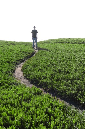 A man standing at the end of a narrow dirt pathway. photo
