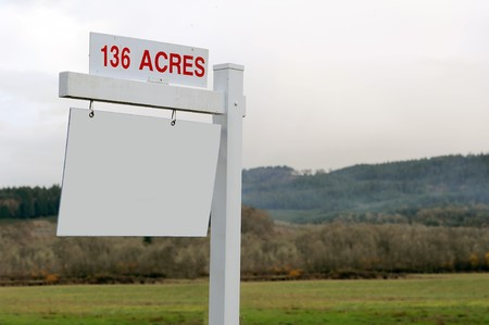 136 acres of land for sale with a blank wooden sign photo