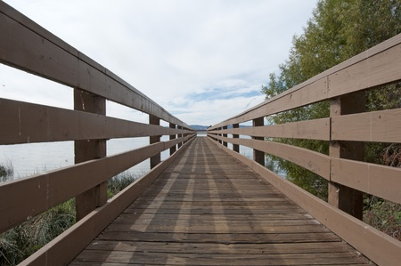A long narrow wooden pier above the calm ocean water with railing. photo