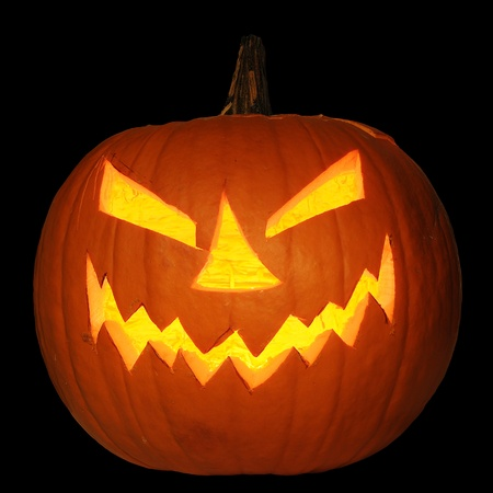 Scary halloween pumpkin jack-o-lantern candle lit, isolated on black background Stock Photo