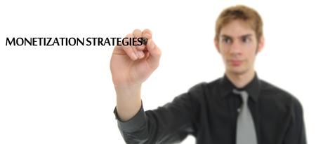 monetization: Businessman writing the phrase Monitization Strategies on blank empty white copyspace isolated on white