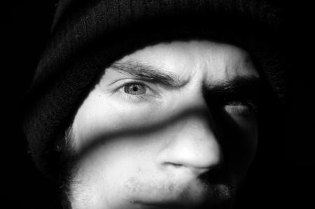 ソート: 問題を抱えた青少年や黒い影の彼を見つめている暗闇の中でいくつかの不気味な話し手刑事ウィンドウまたは刑務所のセル。