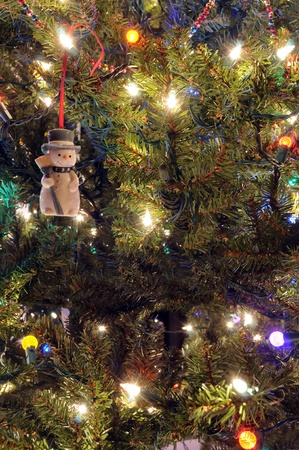Snowman Christmas Ornament hanging on a Christmas Tree with lights photo