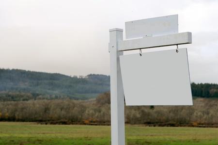 Acres de tierras para la venta con un signo de madera en blanco