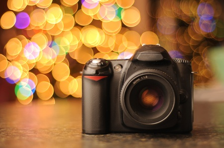 photo studio: DSLR camera sitting on a black countertop with defocused bokeh background. Copyspace with room for your text.