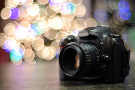 photo studio background: DSLR camera sitting on a black countertop with defocused bokeh background. Copyspace with room for your text.