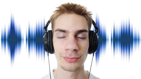Jonge volwassen tiener luistert naar muziek in zijn hoofdtelefoon. Geïsoleerd op een witte achtergrond. Stockfoto