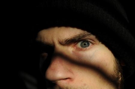 delincuencia: Juventud turbulenta o algunos Penal raro tipo de emisor en la oscuridad negras sombras mirando fijamente a su celda de la ventana o la c�rcel. Foto de archivo