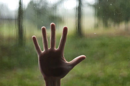 Hand touching a glass window with raindrops over a defocused nature background photo