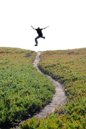 A man jumping above a narrow dirt pathway expressing his freedom. Isolated white blank copyspace above with room for your text. photo