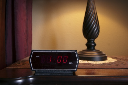 A digital alarm clock displaying 1 pm on the backlit LCD.