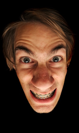 This man is clearly insane. Isolated head on black background. He is wearing braces with a big grin on this face, could be considored a mad scientist. photo