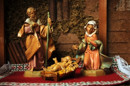 Baby Jesus, Virgin Mary, and Father Joseph in the manger looking upon their newborn son. Nativity figurine decorative display. photo