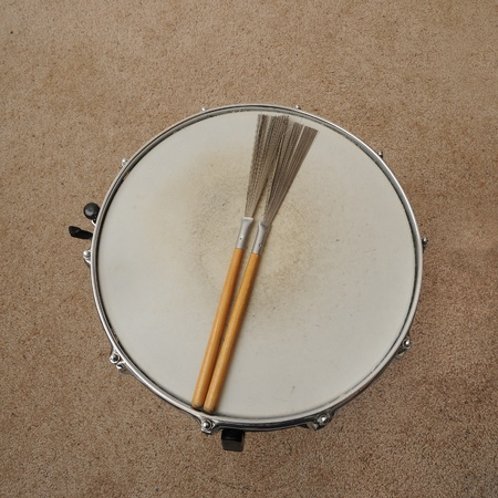 A direct overhead above view of a snare drum on a stand with drum brushes.