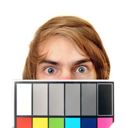 A male production assistant holds up a white balance card with test colors on it to calibrate the colors for photography and videography. photo