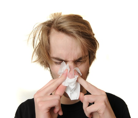 Young man blowing his nose because he is very ill and sick with a cold and fever. Isolated on white background. photo
