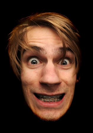 This man is clearly insane. Isolated head on black background. He is wearing braces with a big grin on this face. Stock Photo - 8638416