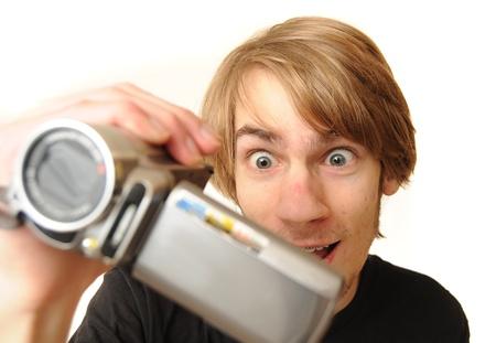 흰 배경에 고립 된 캠코더를 들고 젊은 성인 남자
