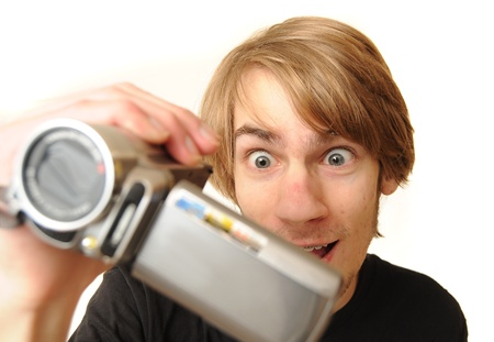 Young adult man holding a camcorder isolated on white background Foto de archivo