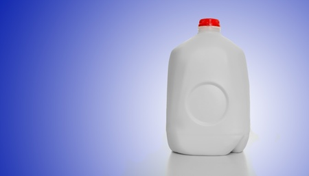 1 Gallon of Milk in a milk carton on a shiny table with blue background background.  photo