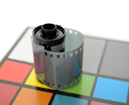 Roll of 35mm Film on top of color calibrated card of squares. photo