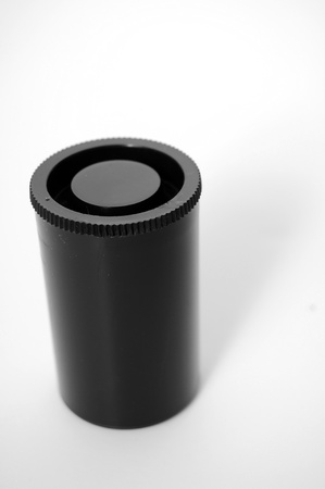 A closeup shot of an old plastic film canister used for holding photography film isolated on white background. photo