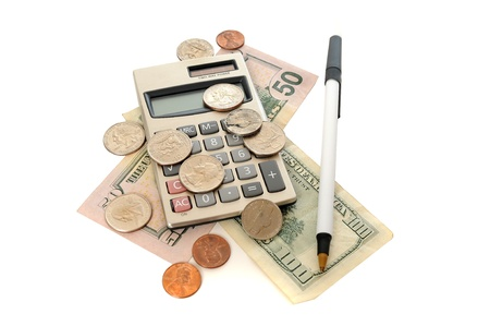write us: Calculator with a twenty dollar bill and a bunch of coins and a pen on a white table. This image demonstrates taxes, accountants, paychecks, business and finance.
