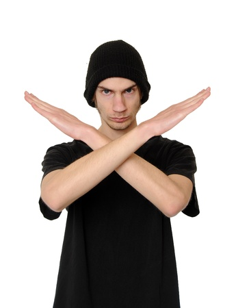Serious and determined young man makes an X shape with his arms and hands. This could mean stop, cross, or