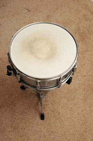 Above view of a snare drum on a stand on a carpet.