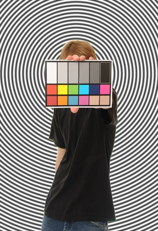 A man holds up an 18 % gray white balance card with test colors on it to calibrate the colors perfectly in post production. photo