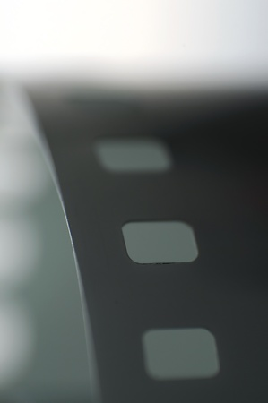 Macro closeup shot of a roll of 35mm film used for photography and movies, isolated on white background