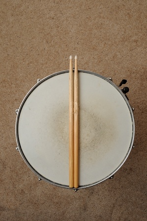 A direct overhead above view of a snare drum on a stand with drum sticks