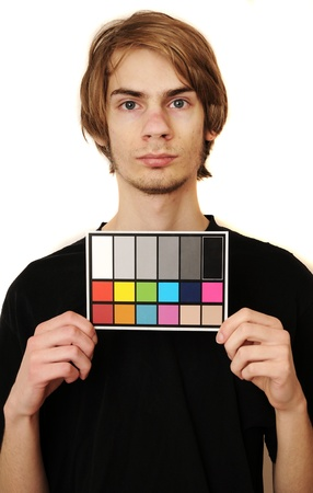 A man holds up an 18 % gray white balance card like he is in a mugshot with test colors on it to calibrate the colors perfectly in post production. photo