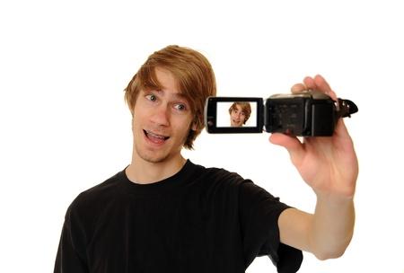 白い背景で隔離の HD ビデオカメラを保持している若い大人の男