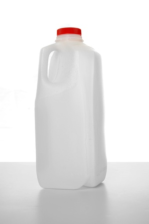 jugs: Milk carton with red label on a shiny table with white background. 1 Liter.