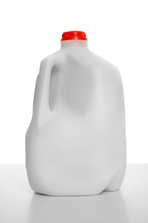 白い背景と光沢のあるテーブルの上のミルクのカートンのミルクの 1 ガロン。