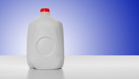1 Gallon of Milk in a milk carton on a shiny table with blue background background.