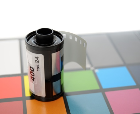 calibrated: Roll of 35mm Film on top of color calibrated card of squares. Stock Photo