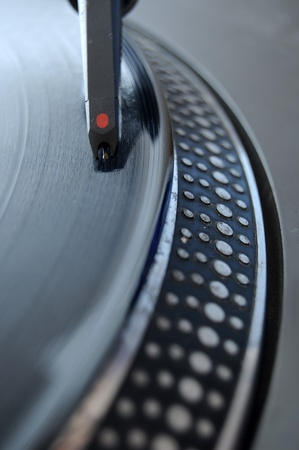 DJ record player with a macro closeup of the stylus on a 12 inch vinyl LP playing hiphop techno rave beats. photo