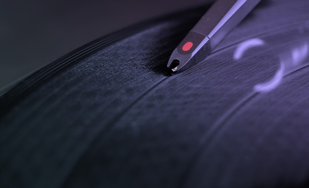 DJ record turntable. Macro closeup of the needle on a 12 inch vinyl LP playing hiphop techno rave beats. photo