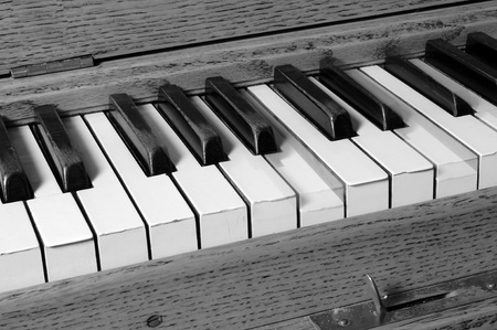 Black and white photo of a piano player with some keys being pressed down photo