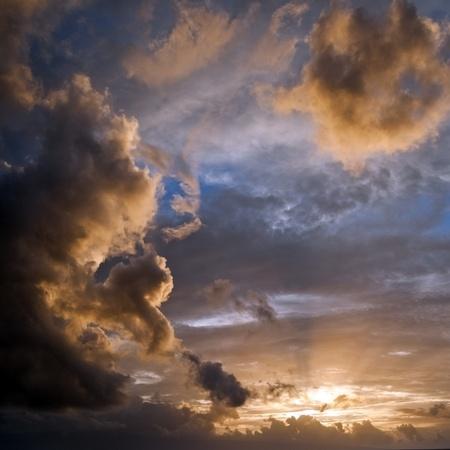 shining through: Cielo azzurro con nuvole retroilluminato giallo provenienti dal sole che splende attraverso con raggi di luce. Piazza composizione di sfondo.