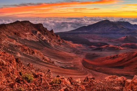 Volcanic crater landscape with beautiful orange clouds at sunrise taken at Haleakala National Park in Maui, Hawaii.