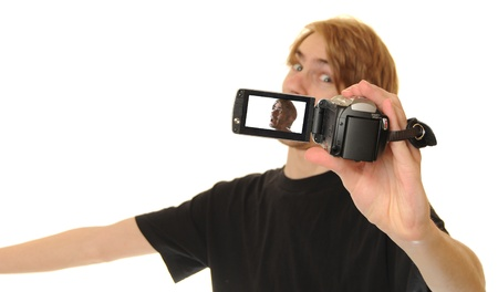 Young adult man holding an HD camcorder in front of his face as he records himself talking. He will then later upload his video content to the internet to show his online audiences his daily personal vlog. Foto de archivo