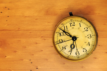 An old classic antique vintage pocket watch on a wooden background with background copyspace to the left.
