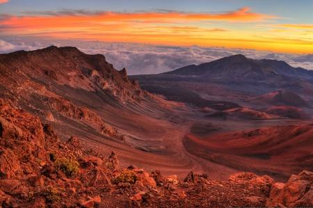 ハワイ マウイ島のハレアカラ国立公園で撮影した日の出の美しいオレンジ雲と火山の噴火口の風景です。